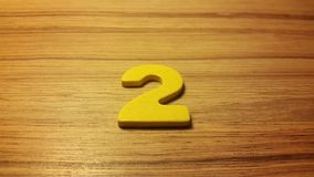 Yellow  number 2 on wooden background Stock Image