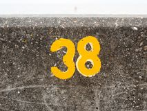 A yellow numbering with paint on sea front wall Harwich 38. England; UK Royalty Free Stock Image