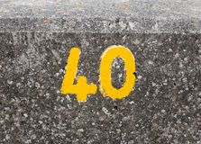 A yellow numbering with paint on sea front wall Harwich 40. England; UK Royalty Free Stock Image