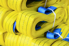 Yellow nylon soft lifting slings stacked in piles. Warehouse of finished products for industrial enterprises Royalty Free Stock Photos