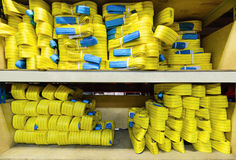 Yellow nylon soft lifting slings stacked in piles. Warehouse of finished products for industrial enterprises Stock Image