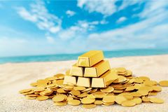 Gold bars and coins on sand beach. Yellow objects background money luxury shiny treasure Stock Photography