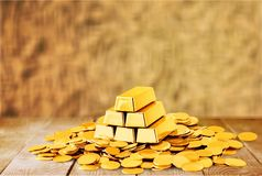 Gold bars and coins on wooden table. Yellow objects background money luxury shiny treasure Stock Photography