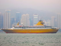 Yellow Ocean Liner in Frontof City Skyline. A yellow ocean cruise liner in front of a major city skyline in Hong Kong Stock Photos