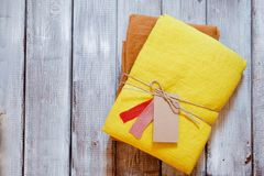 Yellow and ochre linen fabric packed with jute rope. Concept of sewing from natural textile clothing background. Place for text stock image