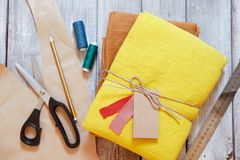 Yellow and ochre linen fabric packed with jute rope. Concept of sewing from natural textile clothing background. Place for text stock photos