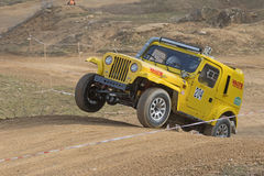 Yellow off road car is jumping in terrain Royalty Free Stock Image