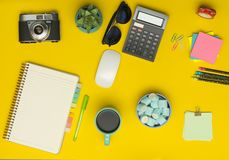 Yellow office desk table with camera, notebook, calculator, cup of coffee royalty free stock images