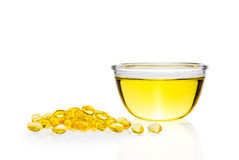 Yellow oil in glass bowl and gel pills, white background Royalty Free Stock Photography