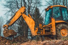 A yellow old excavator in the middle of the forest digs a ladle pit to collect water