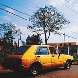 The yellow old-fashioned car running Royalty Free Stock Images