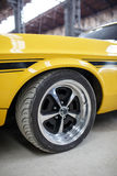 Yellow old muscle car with alloy wheel indoor.  Stock Photos