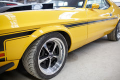 Yellow old muscle car with alloy wheel indoor.  Royalty Free Stock Photography