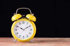 Free Yellow Old Retro Clock On Wooden Desk And Black Background Stock Photos - 130506043
