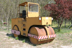 Yellow old road roller parking in the backyard. Rusty road roller parking in grassy backyard rural scene Royalty Free Stock Photography