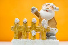 Yellow old time Santa Claus figurine standing behind garden fence and waving with one hand Royalty Free Stock Photo