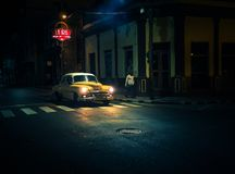 Yellow oldtiemr passes by a bar at night under a street lamp wit. Yellow oldtimer passes a crosswalk at night in front of a bar in santiago de cuba Royalty Free Stock Photos