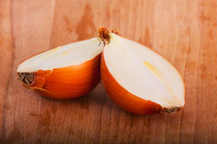 Yellow onion. Two halves of yellow onion on a wooden board Stock Photos