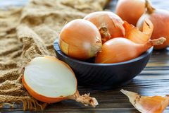 Fresh onion bulbs in a wooden bowl. Royalty Free Stock Photography