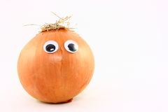 Yellow Onion With Plastic Eyes. A yellow onion decorated with plastic wiggly eyes isolated on a white background Stock Photo