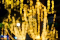 Yellow or Orang Bokeh light on tree of Festival at night time. Abstract or blurred of light glitter. Glow texture background. Yellow or Orang Bokeh light on royalty free stock photo