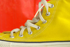 Yellow on orange. Yellow basketball shoe royalty free stock photo