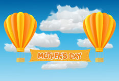 Yellow and orange air ballon with basket. Yellow and orange air ballon with mother day banner fly past clouds Stock Photo