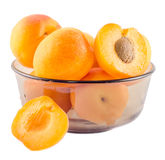 Yellow-orange apricots, half apricot with pip, in a brown transparent bowl Stock Image