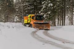 Yellow, Orange, and Black Truck Plowing Snow Stock Photo
