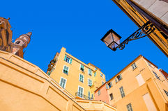 Yellow and orange buildings under blue sky in Menton. stock image