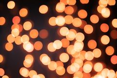 Yellow and orange Christmas tree bokeh on black background of defocused glittering lights, Christmas background pattern concept stock images