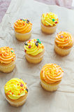 Yellow and orange cupcakes with sprinkles top view Royalty Free Stock Images
