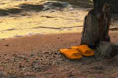 Yellow Orange flipflop on the sandy beach sea water background at sunset. Resorts of the Krasnodar Territory Sea of Azov. YellowOrange flipflop on the sandy royalty free stock image