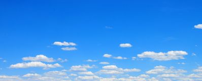 White clouds with Blue sky. White clouds drifting across a bright blue sky royalty free stock photo