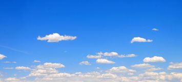 White clouds with Blue Sky. Clouds drifting across a bright blue sky Royalty Free Stock Images