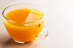 Yellow orange juice. In glass cup standing on wooden table Stock Photo