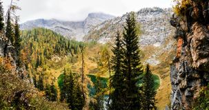 Colorful larch trees with mountains and lake. National Park Berchtesgaden. Royalty Free Stock Image