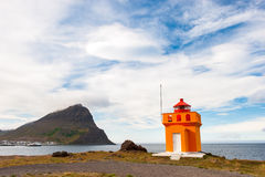 Yellow with orange lighthouse on ocean shore and mountain, Iceland Royalty Free Stock Image