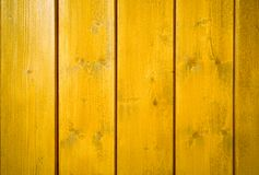 Yellow orange painted wooden wall plank perpendicular to the frame as simple saturated intense yellow color wood background stock photography