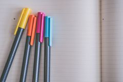 Yellow, Orange, Pink, and Blue Coloring Pens on White Notebook stock photo
