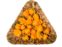 Yellow orange ripe habanero hot chili peppers on a wooden plate Stock Photos