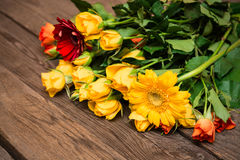 Yellow, orange roses and herberas on a wooden background. Women' Stock Image