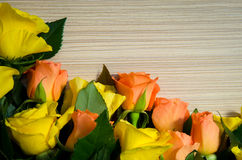 Yellow and orange roses on wooden background Stock Images