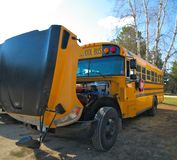 Yellow Orange School Bus with hood open for repairs. Yellow Orange School Bus in parking lot with hood open for service repair is backlit on a sunny day royalty free stock photo