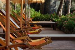 Yellow and orange sunbeds and straw sunshades in Italy Stock Photography
