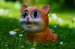 Yellow and Orange Tabby Kitten Figurine on Green Grass Plant Royalty Free Stock Photography
