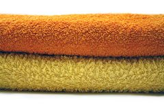 Yellow and orange towel. Towels isolated, towel layers in sauna isolated on white Stock Photos