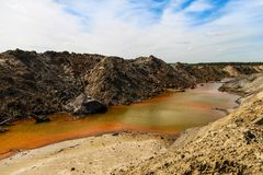 Yellow-orange toxic waste in water in sandpit. Ecology concept stock images