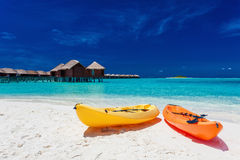 Yellow and orangel kayaks on the tropical beach with vilas Stock Photos