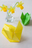 Yellow Origami Easter Bunny. Selective focus image of a yellow origami Easter rabbit with daff flowers in the background royalty free stock image